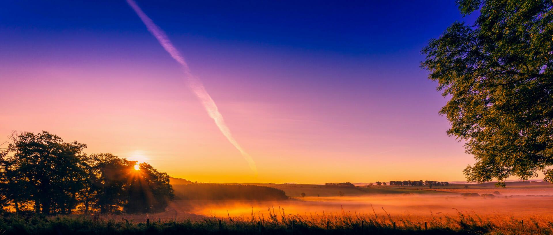 Early morning sun shining on mist over landscape