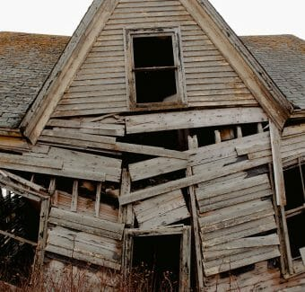 wooden damaged abandoned rustic house in village.  Men's mental health around property ownership.