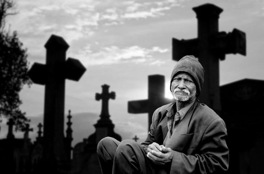 man sitting alone in a graveyard