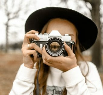 selective focus photography of woman digital nomad using white and black slr camera